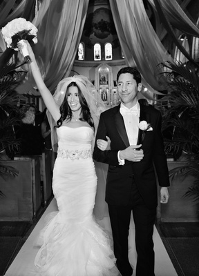 Black and white photo of bride in Vera Wang dress and groom leaving wedding ceremony