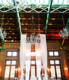 Wedding ceremony in historic building with tall drapery crystal chandeliers wood brick elements