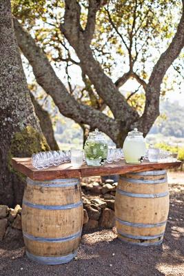 Wedding ceremony outdoor water and lemonade station wine barrels wood decor under tree