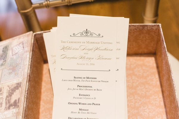 Wedding ceremony program in box with gold lettering and details of proceedings