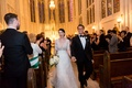 bride in lace v neck carolina herrera, groom in ralph lauren, holds hands walking up aisle