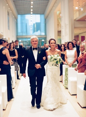 bride in vera wang gown walks down aisle with her father of bride in tuxedo and bow tie