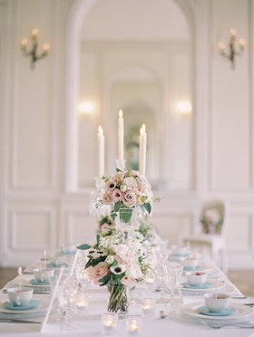 Wedding reception table with votive candles and pink and white roses, lisianthus, white anemones