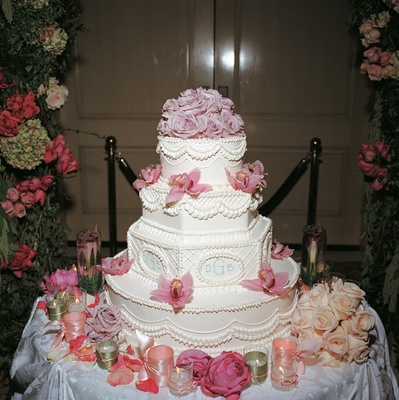 monogrammed wedding cake with pink flowers on sides and top