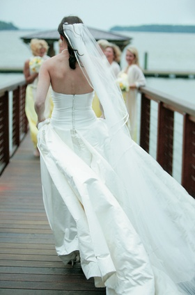 Bride walking down bridge to meet her bridesmaids