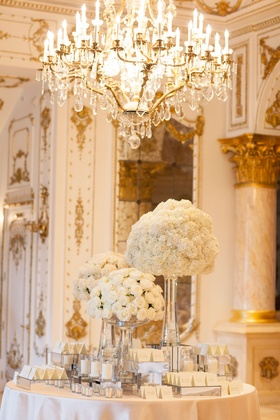 Wedding reception round table with white rose bouquet arrangements tall ceilings chandelier white