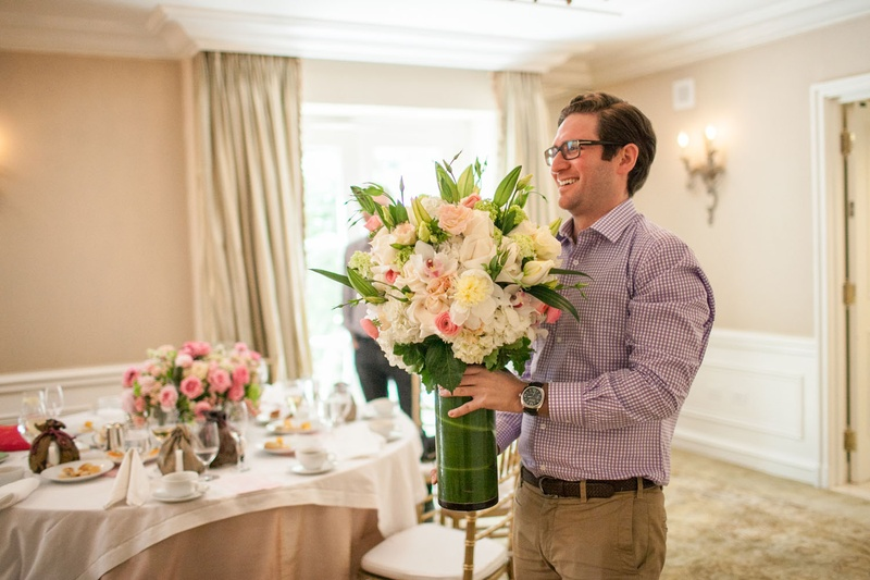 groom to be holding arrangement of pink and white flowers at bridal shower