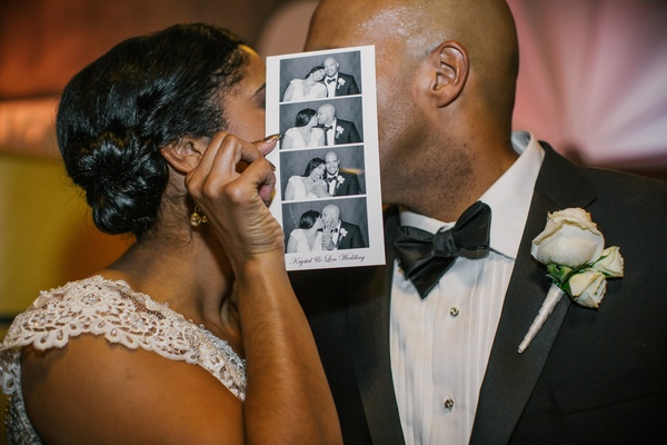 Bride and groom kiss behind photo booth strip