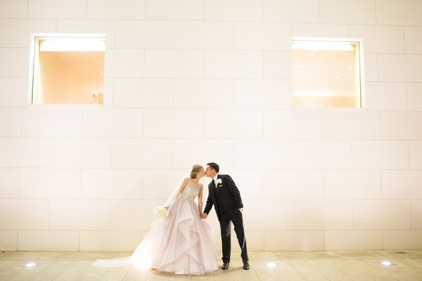 Bride in blush dress kisses groom in tuxedo