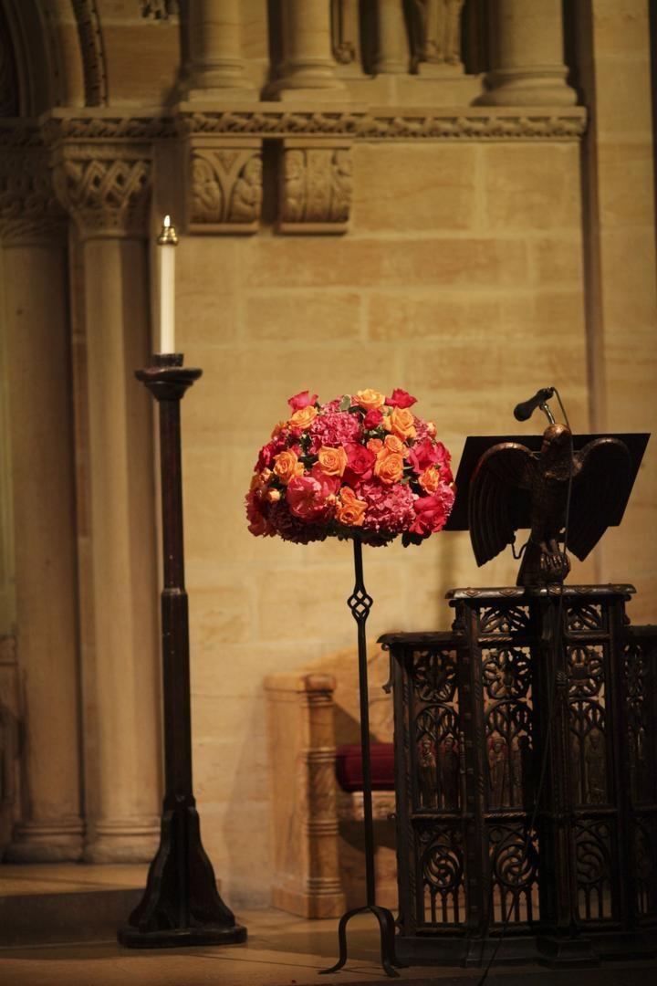 Pink and orange flower arrangement at ceremony podium