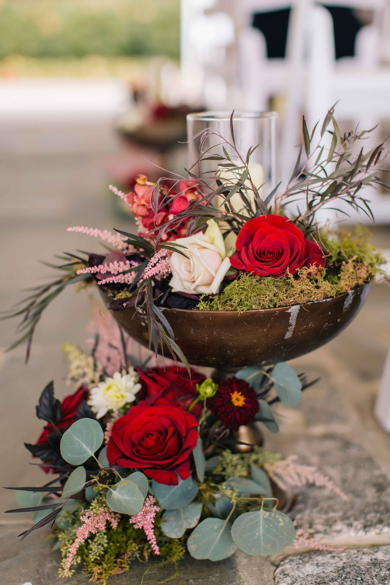 wine-colored flowers and green moss inside a rustic brown vase with sage and olive greenery candles