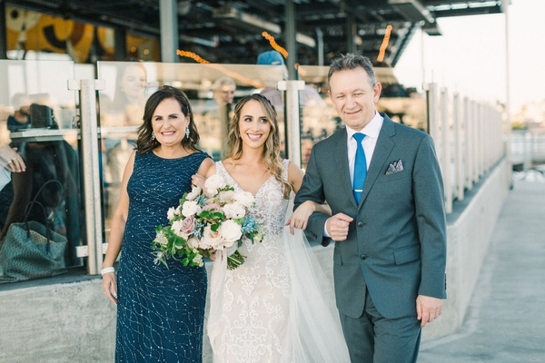bride in lace gown walking arm in arm with her parents, mother of the bride in teal, father in slate