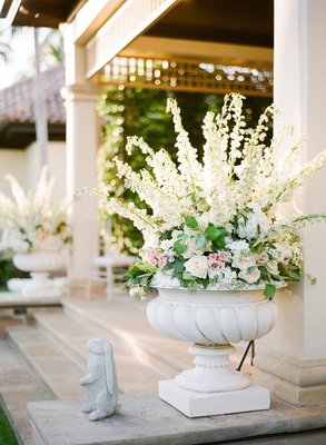 Garden wedding reception with large urn filled with white and pink flowers and greenery
