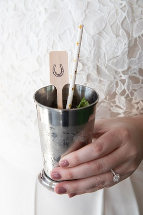 mint julep with paper straw and wooden stir stick with horse shoe
