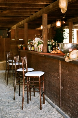 Barstools at rustic country bar for barn wedding