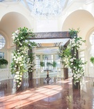 couples wooden tallit chuppah bedecked white flowers green foliage for traditional jewish ceremony