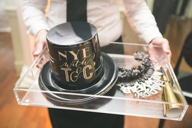 Wedding favors on acrylic tray for NYE wedding black party hat, gold noisemaker, silver headpiece