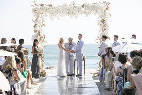 Bride and groom getting married with ocean backdrop