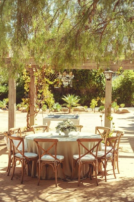 Tan linen round reception table with wood chairs small white flower centerpiece courtyard venue