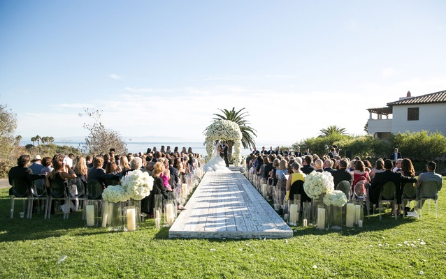 Whitewash wood plank wood aisle with hurricane vases candles white bouquets of flowers arch ocean