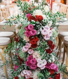 floral runner with pink, burgundy, and lavender roses with ivory hydrangeas and greenery
