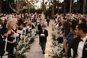 guests looking at cute ring bearers walking down stone aisle ring pillow stripe tie