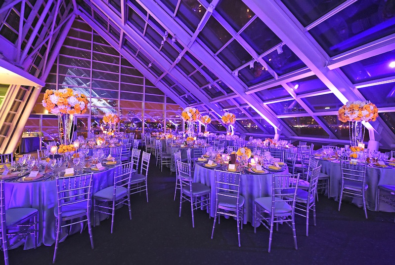 Wedding reception with purple lighting, lilac satin linens, yellow roses, white hydrangeas