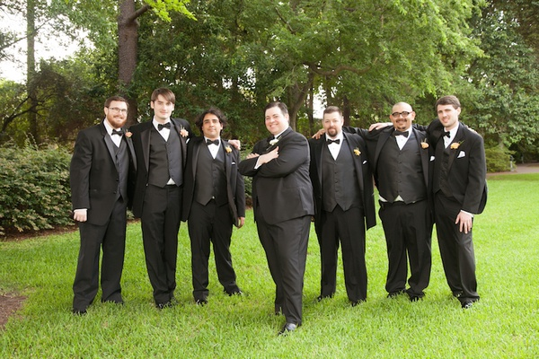 Groom with six groomsmen in tuxedos on grass lawn