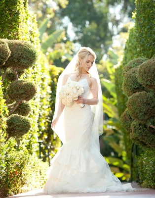 Bridal portrait with bouquet in front of green hedges