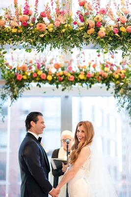 Bride smiles at audience while groom smiles at bride during wedding ceremony officiant jewish