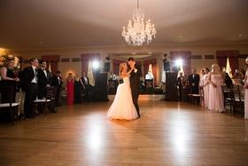 Bride and groom on wood dance floor under chandelier