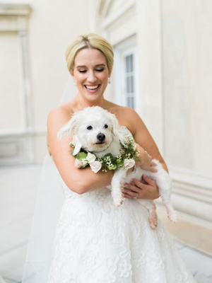 Bride in strapless wedding dress holding white dog with greenery collar flowers