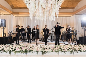 wedding reception live music band at wedding reception flower chandelier flowers in front of stage
