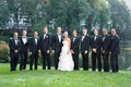 Bride and groom with tux groomsmen in front of lake