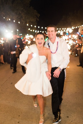 Bride and groom after wedding short strapless dress fur wrap blinky lights and shoes sparklers