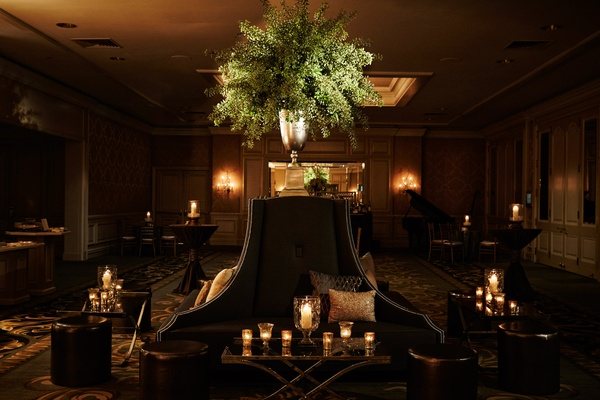 Settees and banquettes at wedding reception ballroom tall greenery arrangements candlelight