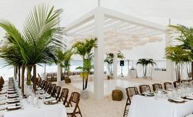 wedding reception on white sand beach bahamas tropical decor green palms white paper lanterns decor