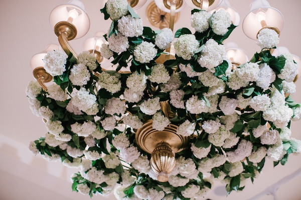 Wedding reception at Montage Laguna Beach with gilt chandelier, pink and white hydrangeas