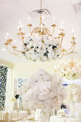 Gold chandelier with white blooms over tables with buffet selections orchids and hydrangeas gold