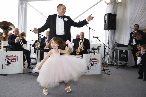 Flower girl in pink flower girl dress dancing with father of bride
