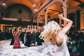 bride tossing bridal bouquet to bridesmaids and girlfriends on dance floor light vibiana
