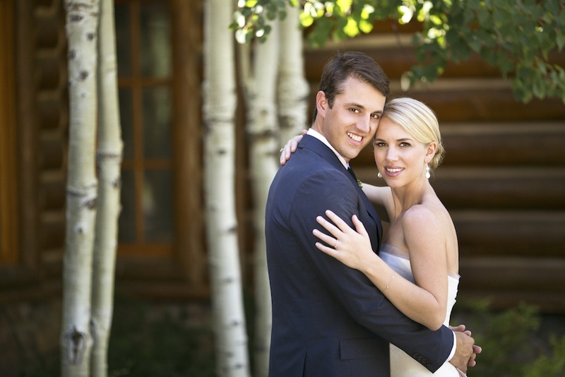 Bride and groom hugging next to log cabin and trees