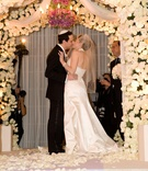 Bride and groom kissing under chuppah