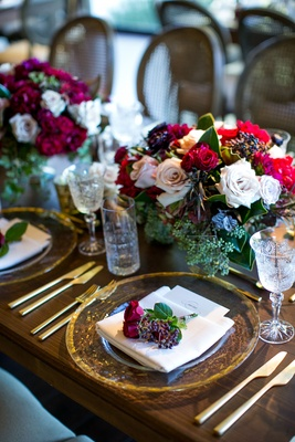 Dark wood tables no linens low flower arrangements centerpieces flowers on top of menu gold charger
