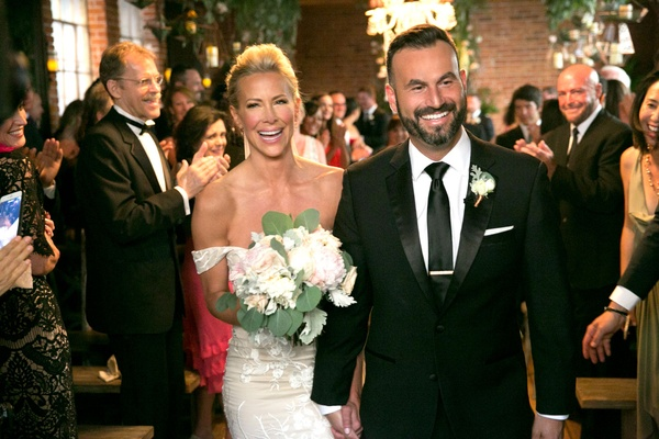 Bride in off the shoulder wedding dress and bouquet holding hands with new husband adam touni