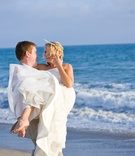 Wedding photo of groom picking up bride on beach