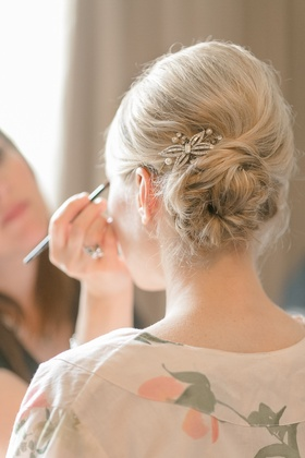 Bride in an off-white robe with pink flowers, side bun with a crystal and pearl hair pin