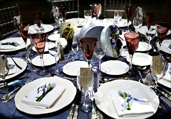 Wedding Reception Table With Blue Tablecloth White Tableware And Red Glassware