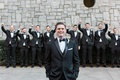Groom in tuxedo and bow tie with cheering groomsmen behind him
