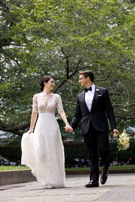 bride in lace v neck carolina herrera, groom in ralph lauren holds hands and bouquet